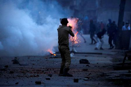 FILE PHOTO: An Indian police officer fires a tear gas shell towards demonstrators, during a protest against the recent killings in Kashmir, in Srinagar May 8, 2018. REUTERS/Danish Ismail/File Photo