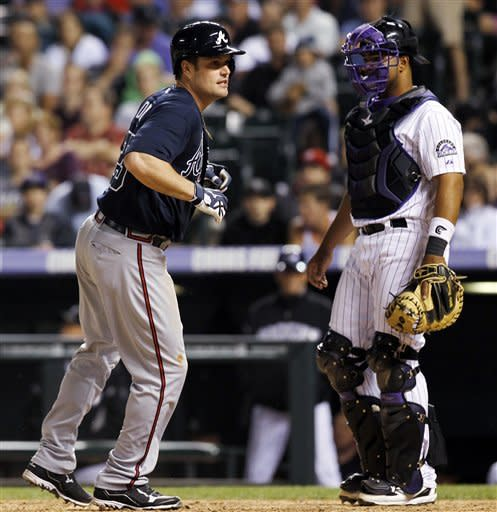 Atlanta Braves' Matt Diaz, left, crosses home plate as Colorado Rockies catcher Wilin Rosario stands by in the seventh inning of a baseball game in Denver, Saturday, May 5, 2012. Diaz scored when the Braves' Michael Bourn drew a walk with the bases loaded. (AP Photo/David Zalubowski)