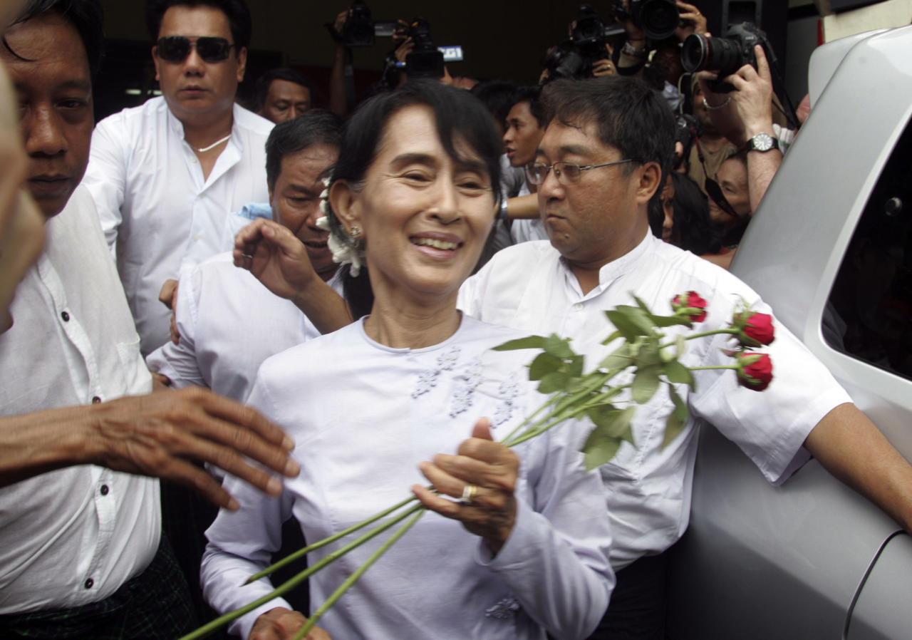 Myanmar pro-democracy leader Aung San Suu Kyi receives flowers from supporters as she leaves the headquarters of her National League for Democracy party in Yangon, Myanmar Monday, April 2, 2012. Suu Kyi claimed victory Monday in Myanmar's historic by-election, saying she hoped it will mark the beginning of a new era for the long-repressed country. (AP Photo/Khin Maung Win)