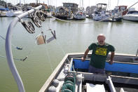 Salmon fisherman Mike Hudson stands at the back of his boat at the Berkeley, Calif., Marina on Thursday, July 22, 2021. Baby salmon are dying by the thousands in one river and an entire run of endangered salmon could be wiped out in another. The plummeting catch has led to skyrocketing retail prices for salmon, hurting customers who say they can no longer afford the $35 per pound of fish, said Hudson, who has spent the last 25 years catching and selling salmon at farmers' markets in Berkeley. (AP Photo/Eric Risberg)
