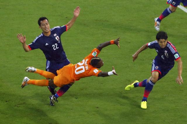 Ivory Coast's Geoffroy Serey Die falls as he fights for the ball with Japan's Maya Yoshida during their 2014 World Cup Group C soccer match at the Pernambuco arena in Recife June 14, 2014. REUTERS/Ruben Sprich (BRAZIL - Tags: TPX IMAGES OF THE DAY SOCCER SPORT WORLD CUP)