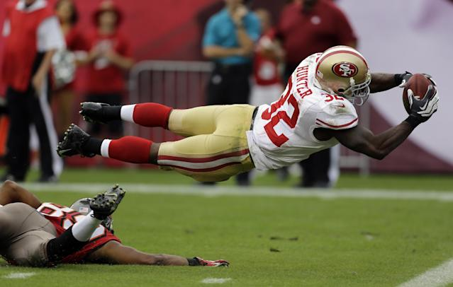 San Francisco 49ers' Kendall Hunter (32) dives into the end zone to score after picking up a fumble by Tampa Bay Buccaneers' Russell Shepard during the fourth quarter of an NFL football game Sunday, Dec. 15, 2013, in Tampa, Fla. (AP Photo/Chris O'Meara)