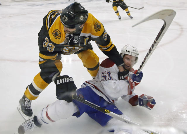 Boston Bruins defenseman Zdeno Chara (33) takes down Montreal Canadiens center David Desharnais (51) during the second overtime period in Game 1 of an NHL hockey second-round playoff series in Boston, Thursday, May 1, 2014. (AP Photo/Elise Amendola)