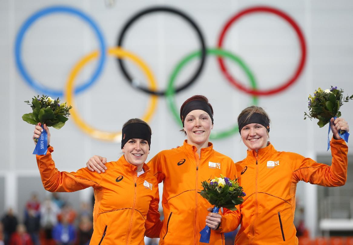 Athletes from the Netherlands, from left to right, silver medallist Ireen Wust, Gold medallist Jorien ter Mors and bronze medallist Lotte van Beek celebrate during the flower ceremony for the women's 1,500-meter speedskating race at the Adler Arena Skating Center during the 2014 Winter Olympics in Sochi, Russia, Sunday, Feb. 16, 2014. (AP Photo/Pavel Golovkin)