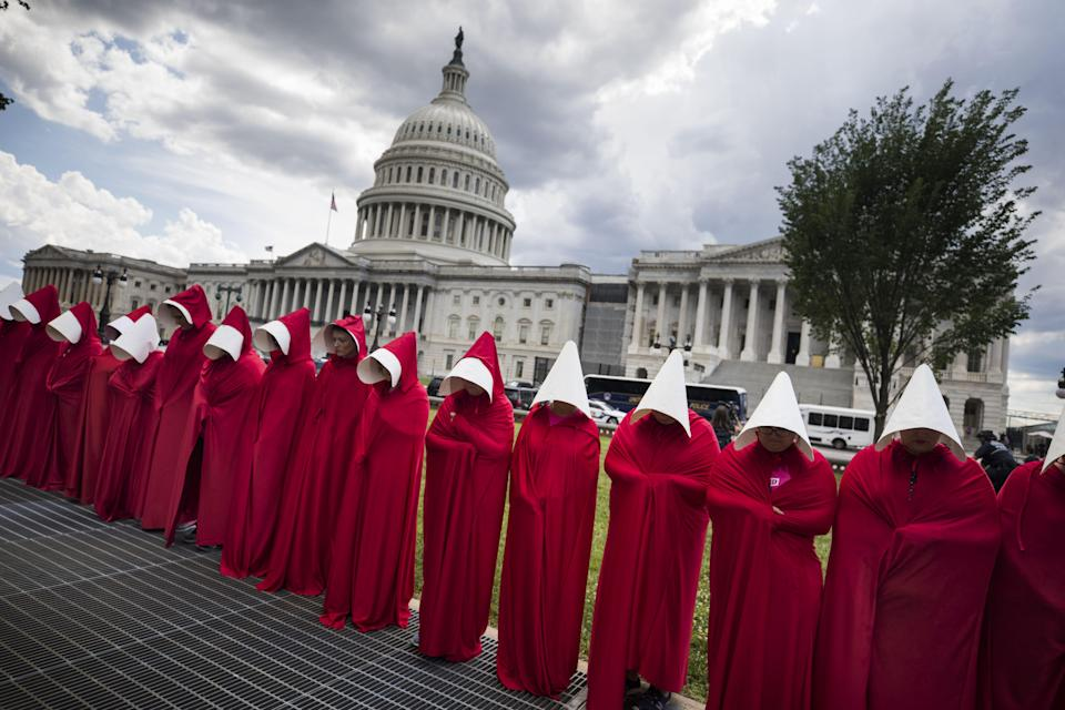 People protesting outside the U.S. Capitol wearing costumes inspired by <em>The Handmaid's Tale.</em> (Photo: Shutterstock)