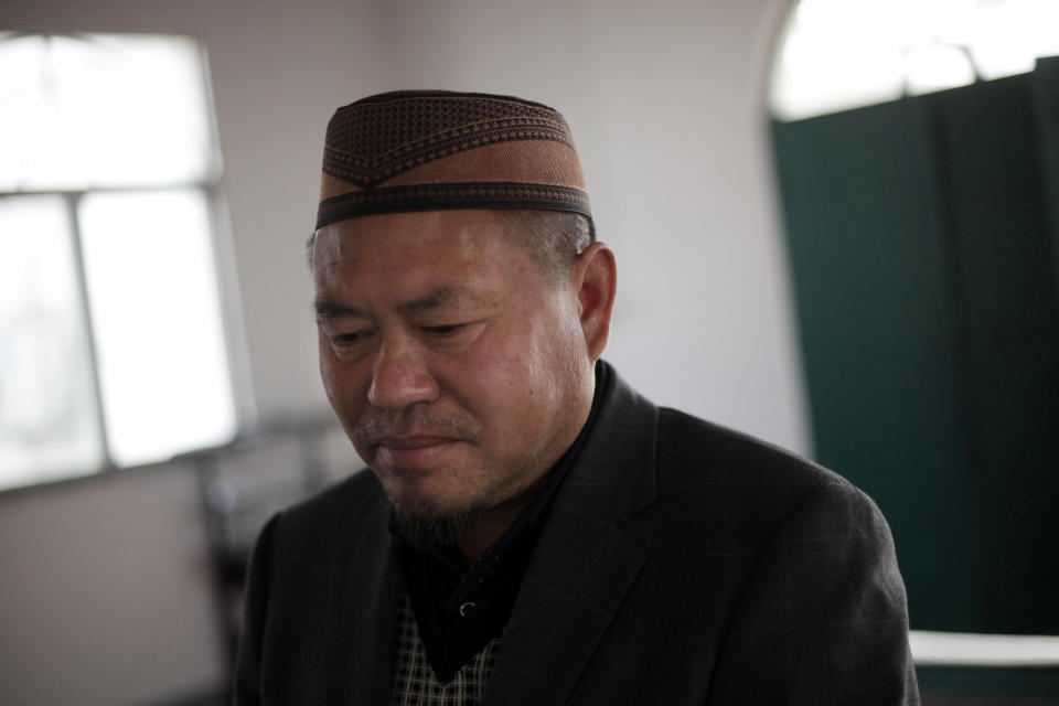 In this March 18, 2017 photo, Tao Yingsheng, the imam at the Nangang mosque, stands in the mosque in Hefei in central China's Anhui province. On the dusty plains of the Chinese heartland, the bitter fight over the mosque illustrates how a surge in anti-Muslim sentiment online is spilling over into the real world. If left unchecked, scholars say, such attitudes risk inflaming simmering ethnic tensions that have in past erupted in bloodshed. (AP Photo/Gerry Shih)