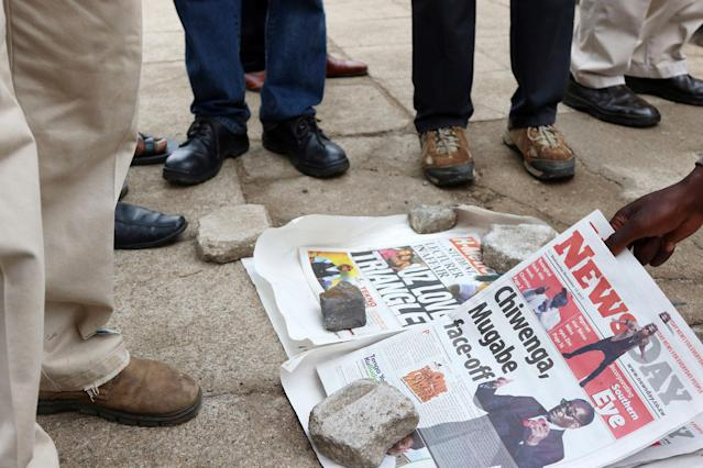 <p>Zimbabweans check newspapers as armed soldiers patrol the streets in Harare, Wednesday, Nov. 15, 2017. (Photo: AP) </p>