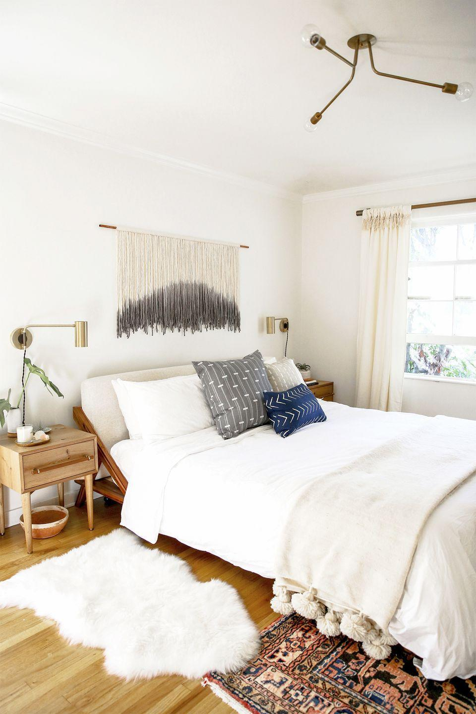 <p>To add dimension to an all-white bedroom, bring in different textures with a faux fur rug and macrame wall hanging.</p>