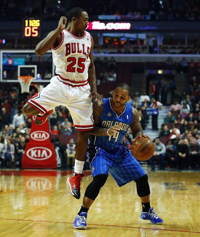 Chicago Bulls point guard Marquis Teague (25) runs into Orlando Magic point guard Jameer Nelson (14) during the first half of an NBA basketball game in Chicago on Monday, Dec. 16, 2013. (AP Photo/Jeff Haynes)