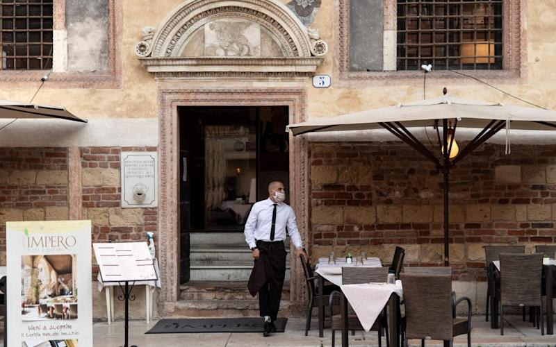 A waiter wearing a protective face mask stands outside a restaurant in Piazza dei Signori in Verona, northern Italy. - AFP
