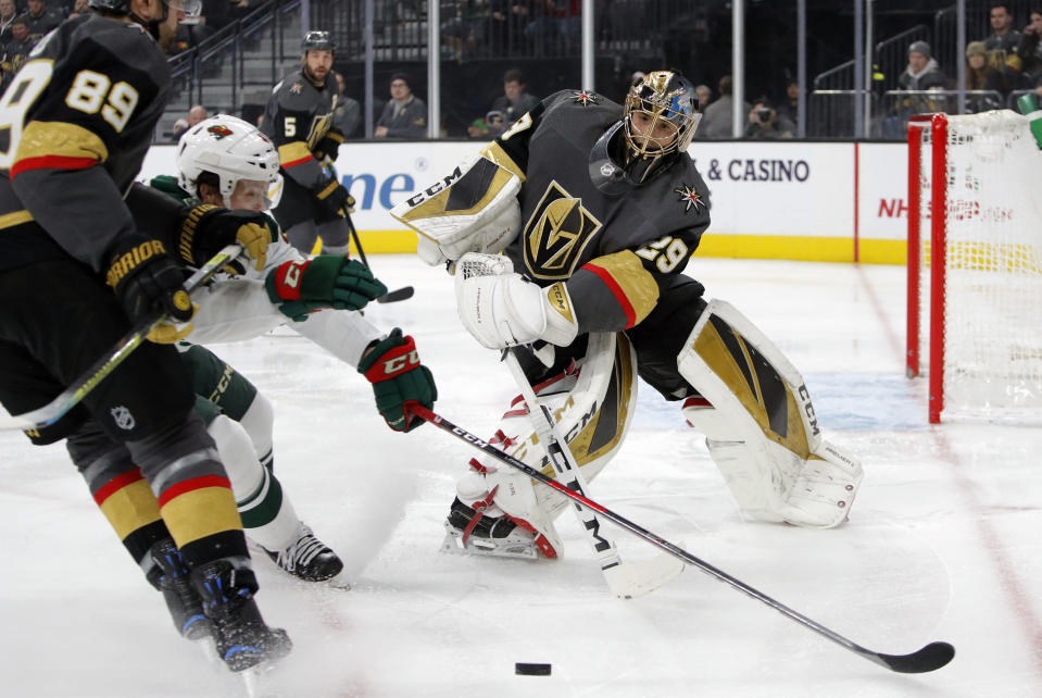 Vegas Golden Knights goaltender Marc-Andre Fleury (29) knocks the puck away against the Minnesota Wild during the first period of an NHL hockey game Tuesday, Dec. 17, 2019, in Las Vegas. (AP Photo/John Locher)