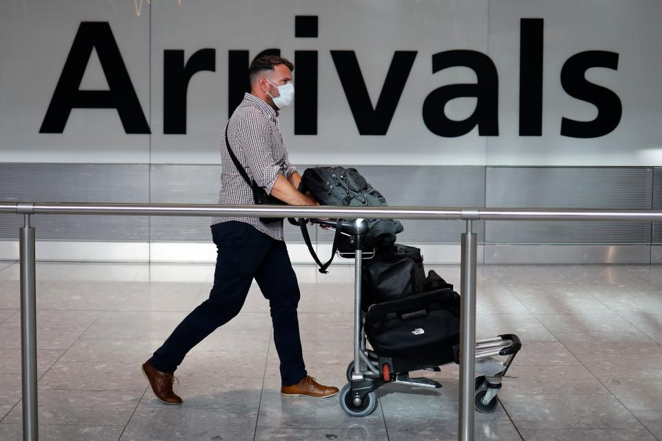 A passenger wearing a face mask as a precaution against the novel coronavirus arrive at Heathrow airport, west London, on May 22, 2020. - Travellers arriving in Britain will face 14 days in quarantine from next month to prevent a second coronavirus outbreak, the government announced on Friday, warning that anyone breaking the rules faced a fine or prosecution. (Photo by Tolga Akmen / AFP) (Photo by TOLGA AKMEN/AFP via Getty Images)