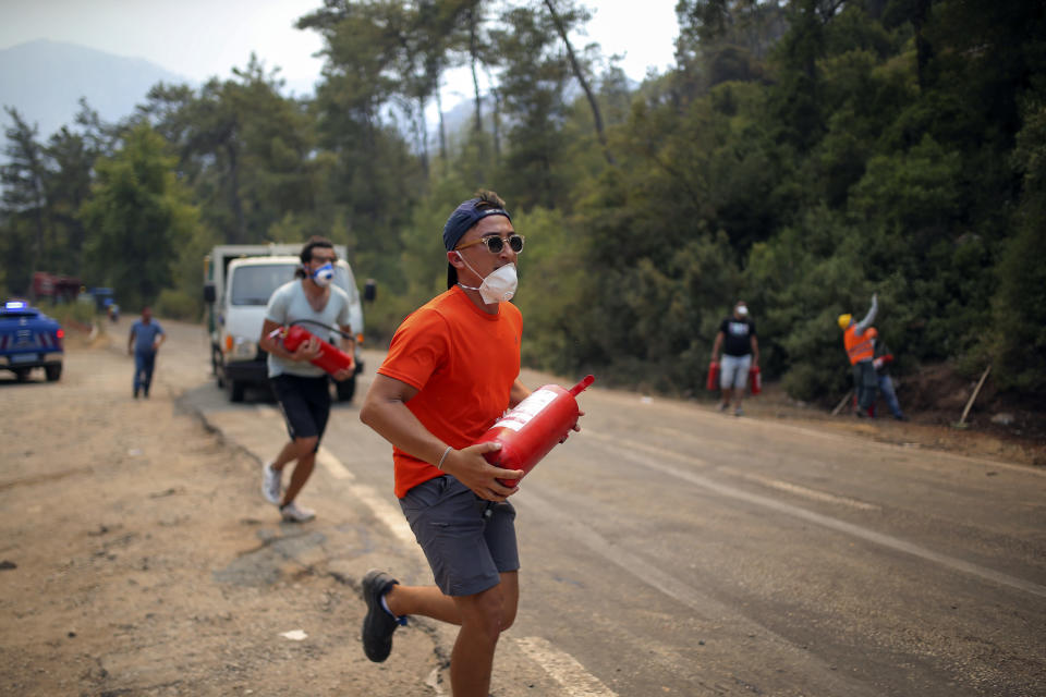 A Turkish volunteer runs as they head to fight wildfires in Turgut village, near tourist resort of Marmaris, Mugla, Turkey, Wednesday, Aug. 4, 2021. As Turkish fire crews pressed ahead Tuesday with their weeklong battle against blazes tearing through forests and villages on the country's southern coast, President Recep Tayyip Erdogan's government faced increased criticism over its apparent poor response and inadequate preparedness for large-scale wildfires.(AP Photo/Emre Tazegul)
