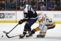 Colorado Avalanche right wing Valeri Nichushkin, left, tries to keep the puck from Nashville Predators center Rocco Grimaldi during the third period of an NHL hockey game Thursday, Nov. 7, 2019, in Denver. Colorado won 9-4. (AP Photo/David Zalubowski)