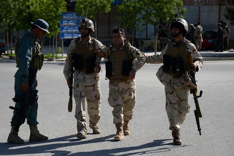 Afghan security personnel assist a colleague during an attack by gunmen at a court complex in Mazar-i-sharif on April 9, 2015 (AFP Photo/Farshad Usyan)