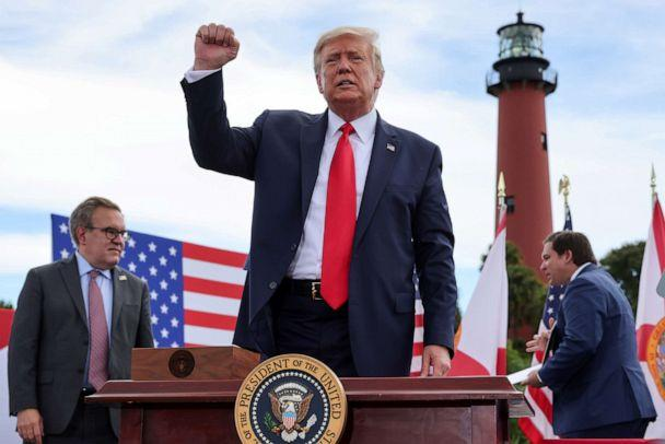 PHOTO: President Donald Trump pumps his fist in front of a crowd of Trump supporters as U.S. Environmental Protection Agency Director Andrew Wheeler and Florida Governor Ron DeSantis look on in Jupiter, Fla., Sept. 8, 2020. (Jonathan Ernst/Reuters)