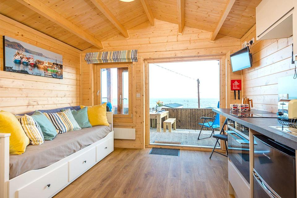 """<p>Located on Monmouth beach between Sidmouth and Weymouth, the adorable chalet overlooks Lyme Bay and has views across the Dorset coastline. </p><p>The cosy spot is equipped with a three seater day bed, a kitchen, a fold out breakfast bar, shower room and a deck with a picnic bench and beach chairs. With nearby beaches including those of Charmouth, Chesil and Weymouth, you'll have plenty of seaside spots to choose from for a picnic or even a dip in the sea (if you're brave). </p><p><strong>Chalet for three people from £405</strong></p><p><a class=""""link rapid-noclick-resp"""" href=""""https://go.redirectingat.com?id=127X1599956&url=https%3A%2F%2Fwww.toadhallcottages.co.uk%2Fholiday-cottages%2Fthe-lobster-pot%2F2392&sref=https%3A%2F%2Fwww.elle.com%2Fuk%2Flife-and-culture%2Fculture%2Fg33261665%2Fcoastal-cottages%2F"""" rel=""""nofollow noopener"""" target=""""_blank"""" data-ylk=""""slk:BOOK ONLINE"""">BOOK ONLINE</a></p>"""