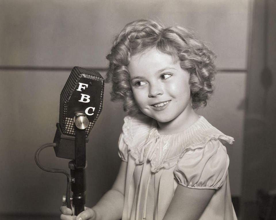 <p>Shirley Temple holding onto a broadcast microphone. </p>