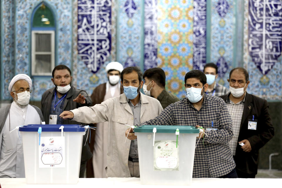 Iranian election official prepare ballot boxes at a polling station in Tehran, Iran, Friday, June 18, 2021. Iran began voting Friday in a presidential election tipped in the favor of a hard-line protege of Supreme Leader Ayatollah Ali Khamenei, fueling public apathy and sparking calls for a boycott in the Islamic Republic. (AP Photo/Ebrahim Noroozi)