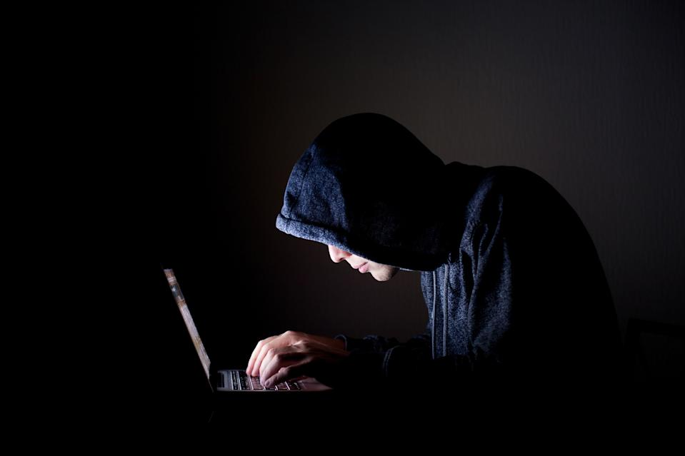 Hooded man in front of a computer.