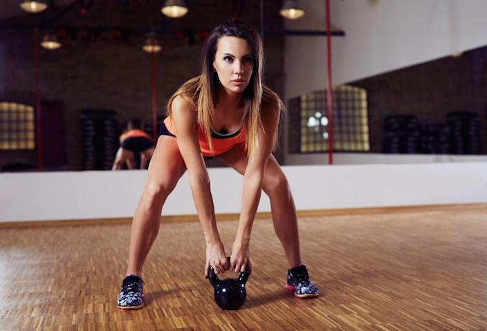 Young woman working out with kettlebell, kettlebell swing exercise at gym
