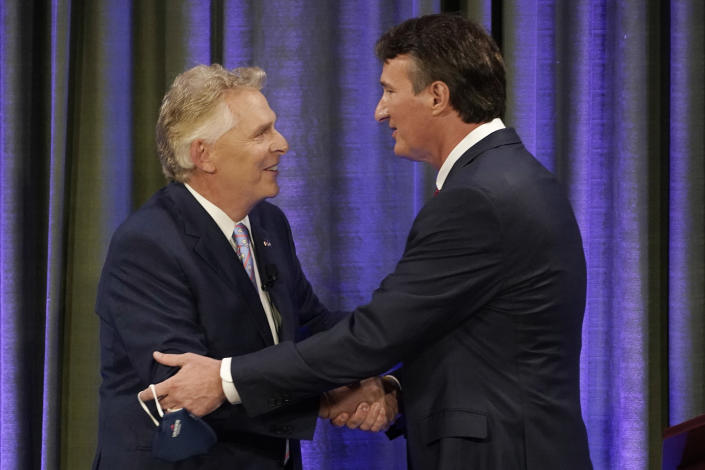 Democratic gubernatorial candidate former Governor Terry McAuliffe, left, greets Republican challenger, Glenn Youngkin, at the start of a debate at the Appalachian School of Law in Grundy, Va., Thursday, Sept. 16, 2021. (AP Photo/Steve Helber)