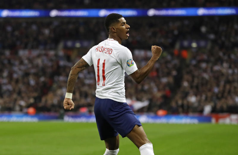 FILE - In this Thursday, Nov. 14, 2019 file photo England's Marcus Rashford celebrates scoring his side's fourth goal during the Euro 2020 group A qualifying soccer match between England and Montenegro at Wembley stadium in London. British Prime Minister Boris Johnson made an abrupt about-face Tuesday June 16, 2020 and agreed to keep funding meals for needy pupils over the summer holidays, after a campaign headed by young soccer star Marcus Rashford. The Manchester United and England player has been pressing the government not to stop a meal voucher program at the end of the school term in July. (AP Photo/Kirsty Wigglesworth, File)