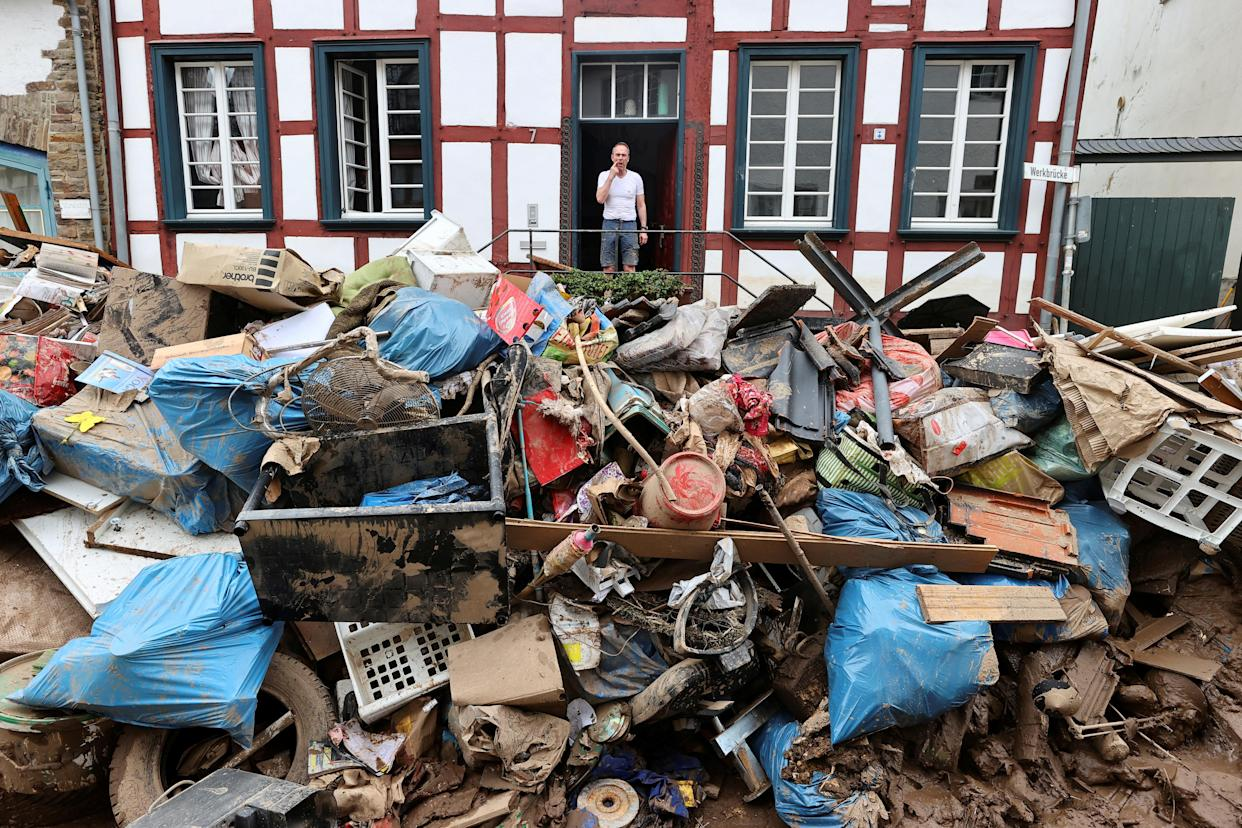 A man stands at the entrance of a home looking out at a giant mound of debris