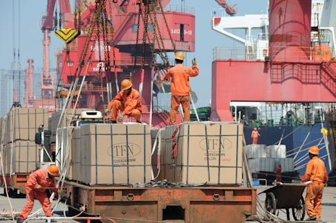 Workers load goods for export onto a crane at a port in Lianyungang, Jiangsu province, China on June 7. Photo: Reuters