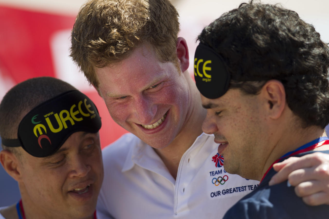 Britain's Prince Harry hugs two blind men after presenting them with medals in Rio de Janeiro, Brazil, Saturday March 10, 2012. Harry is in Brazil at the request of the British government on a trip to promote ties and emphasize the transition from the upcoming 2012 London Games to the 2016 Olympics in Rio de Janeiro. (AP Photo/Felipe Dana)