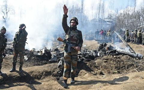 Indian soldiers gesture near the remains of an Indian Air Force helicopter after it crashed in Budgam district, outside Srinagar on February 27, 2019 - Credit: Tauseef Mustafa/AFP