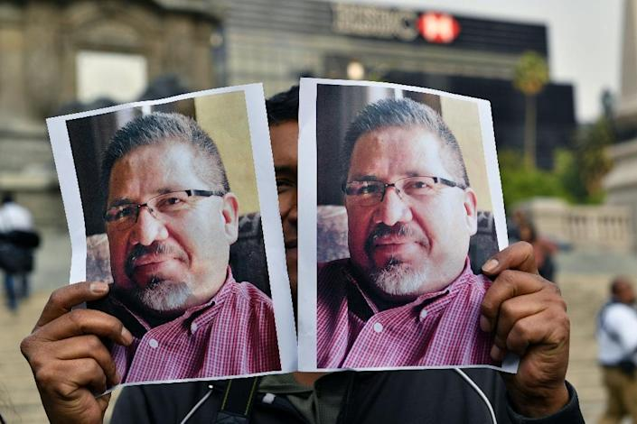 A photojournalist shows pictures of Mexican journalist Javier Valdez, murdered a day earlier, during a protest in Mexico City on May 16, 2017 (AFP Photo/YURI CORTEZ)