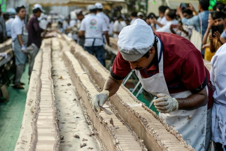 About 1,500 bakers and chefs prepared the serpentine dessert atop thousands of tables and desks (AFP Photo/Arun SANKAR                        )