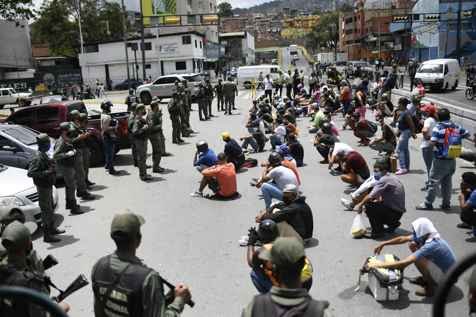 Members of the Bolivarian National Guarde explain proper mask use to non-compliant pedestrians and peddlers on a street of the Petare neighborhood of Caracas, Venezuela, Wednesday, July 29, 2020, amid efforts to contain the spread of the new coronavirus. (AP Photo/Matias Delacroix)