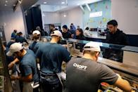 Workers prepare orders in the kitchen at a Chopt Creative Salad Co., location in New York