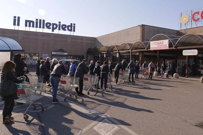 People queue outside a supermarket in Casalpusterlengo, Northern Italy, Monday, Feb. 24, 2020.