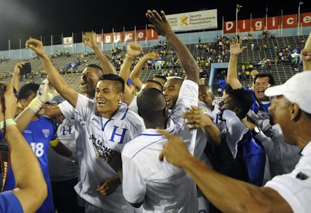 Honduras soccer players celebrate at the end of a 2014 World Cup qualifying match against Jamaica in Kingston, Jamaica, Tuesday, Oct. 15, 2013. The game ended 2-2 and Honduras reached the World Cup in Brazil. (AP Photo/Collin Reid)