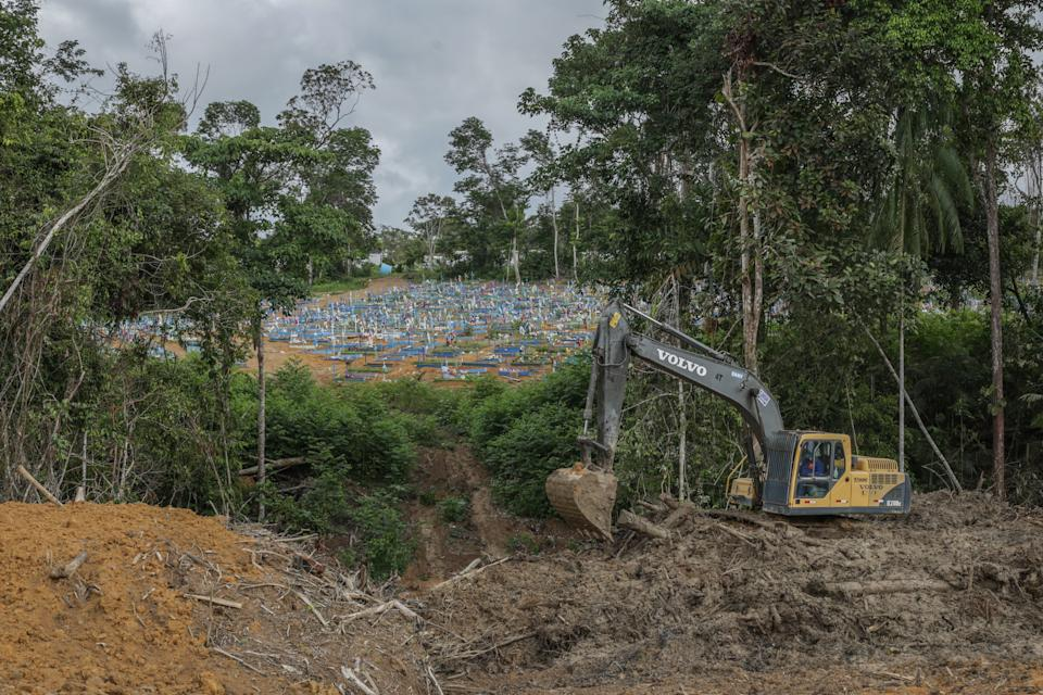 MANAUS, BRAZIL - MAY 19: A tractor removes mud of a new area for burials at the Parque Taruma cemetery on May 19, 2020 in Manaus, Brazil. Brazil has over 260,000 confirmed cases and more than 17,000 deaths caused by coronavirus (COVID-19) pandemic. (Photo by Andre Coelho/Getty Images)
