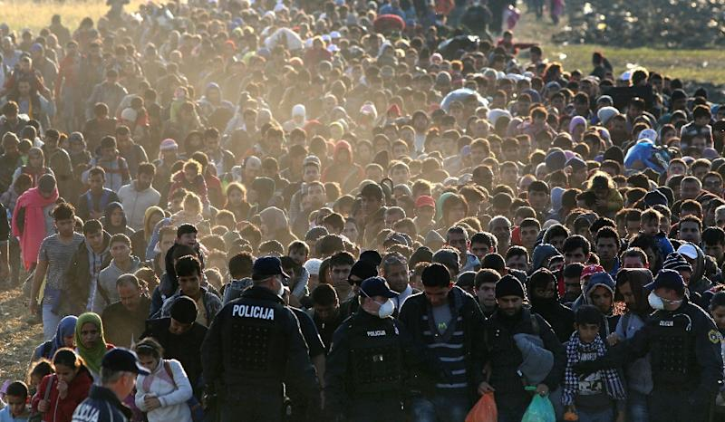 Migrants and refugees are escorted by Slovenian soldiers and police officers as they walk towards a refugee camp after crossing the Croatian-Slovenian border near Rigonce, Slovenia, on October 26, 2015