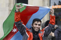 An Azerbaijani man with the national flag celebrates after the country's President claimed Azerbaijani forces have taken Shushi, a key city in the Nagorno-Karabakh region that has been under the control of ethnic Armenians for decades in Baku, Azerbaijan, Sunday, Nov. 8, 2020. (AP Photo)