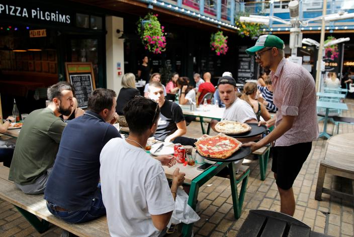 """A waiter serves customers' their pizzas as diners sit at tables outside a restaurant in London on August 3, 2020, as the Government's """"Eat out to Help out"""" coronavirus scheme to get consumers spending again gets underway. - Britain's """"Eat out to Help out"""" scheme began Monday, introduced last month by Chancellor Rishi Sunak to help boost the economy claw its way from a historic decline sparked by the coronavirus crisis. (Photo by Tolga AKMEN / AFP) (Photo by TOLGA AKMEN/AFP via Getty Images)"""