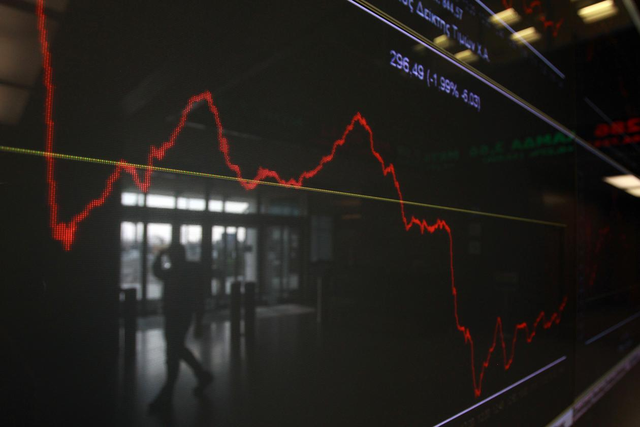 An employee of the Stock Exchange is reflected in a chart displaying stock prices in Athens.