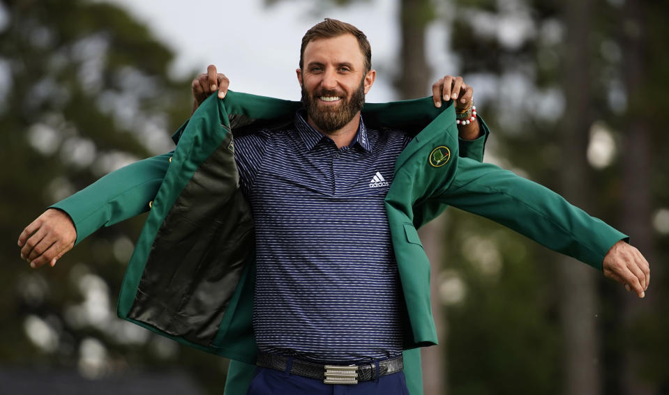 FILE - Tiger Woods helps Masters champion Dustin Johnson with his green jacket after his victory at the Masters golf tournament in Augusta, Ga., in this Nov. 15, 2020, file photo. No one else ever won the Masters and then didn't play in another tournament the rest of the year. No other Masters champion was allowed to keep his green jacket for only five months before it was time to try to win it again. Then again, no one ever played the Masters in November. (AP Photo/Matt Slocum, File)