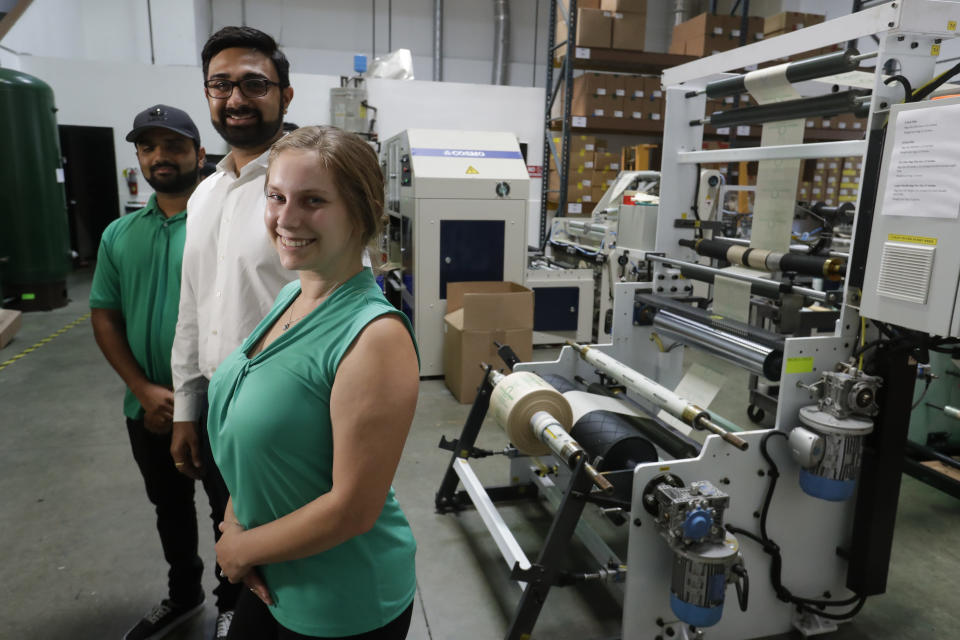 In this Friday, July 5, 2019, photo Achyut Patel, Director of Operations, Rudy Patel, Director of Business Development an Katrina Hart, business development coordinator pose for a picture at beyond Green, a maker of biodegradable bags in Lake Forest, Calif. (AP Photo/Chris Carlson)