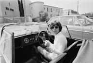 <p>Mick Jagger at the wheel of his Morgan Plus 8 Roadster, outside the Hotel Byblos in Saint-Tropez, France, May 1971.</p>