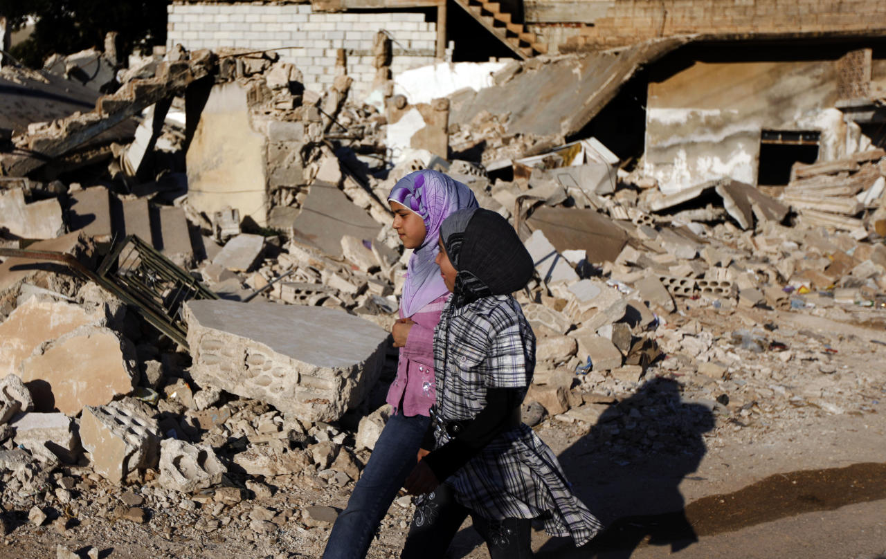 FILE - In this Tuesday, June 5, 2012 file photo, Syrian girls walk by the rubble of a house which was destroyed during a military operation by the Syrian pro-Assad army in April 2012 , in the town of Taftanaz, 15 kilometers east of Idlib, Syria. At dawn on April 3, Syrian forces shelled the town in the first volley of what residents say was a massive assault after a string of large protests calling for the end of the autocratic rule of President Bashar Assad. (AP Photo/Khalil Hamra, File)