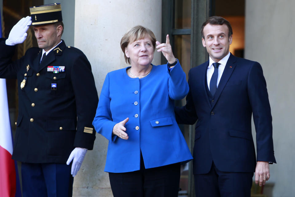 French President Emmanuel Macron welcomes German Chancellor Angela Merkel at the Elysee Palace, Monday, Dec. 9, 2019 in Paris. The leaders of Russia, Ukraine, Germany and France meet to try to seek a settlement for the five-year conflict in eastern Ukraine that has killed 13,000 people. (AP Photo/Rafael Yaghobzadeh)