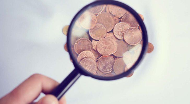 A hand holding a magnifying glass over pennies