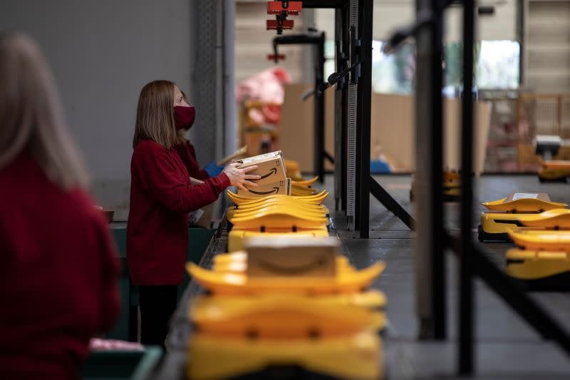 An employee places a parcel on a robot at the Hellenic Post's sorting centre in Kryoneri