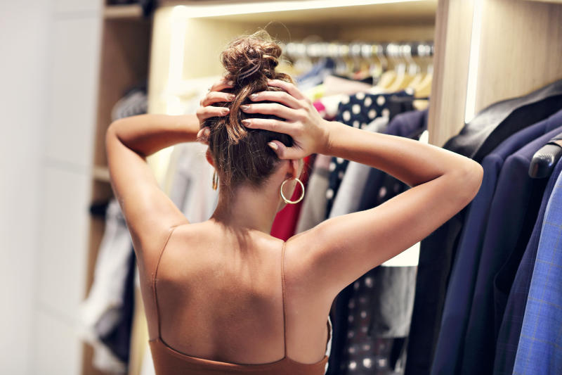 Picture of woman thinking what to dress in walk-in closet